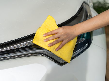 hand with microfiber cloth cleaning a car