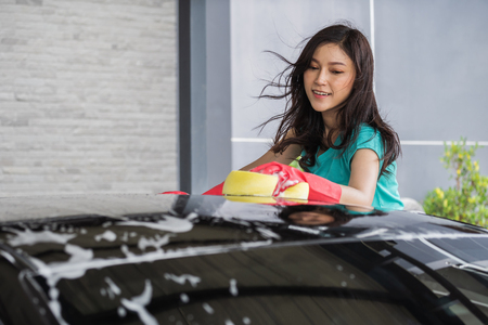 woman washing the roof of the car with sponge Archivio Fotografico