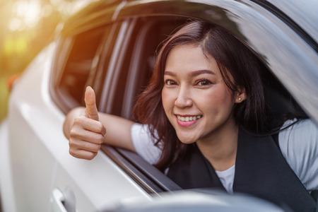 beautiful woman giving thumb up inside her car