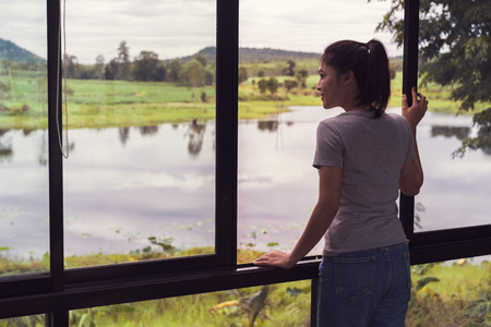 woman open window and looking to nature view
