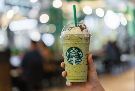 NAKHON RATCHASIMA, THAILAND - 28 SEP 2018 : hand holding glass of Green tea frappe with whipped-cream at Starbucks coffee shop in Teminal 21 Mall at Nakhon Ratchasima, Thailand Editorial