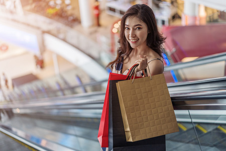 happy young woman with shopping bags on escalator in mall