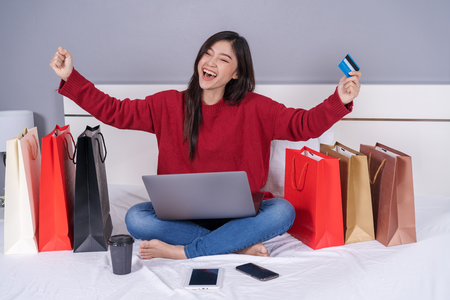 cheerful woman using laptop computer to shopping online on a bed Stock fotó
