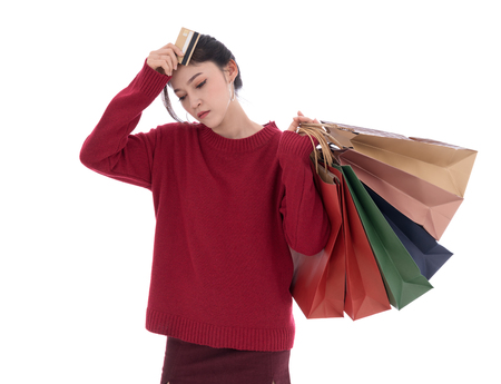 stressed woman holding credit card and shopping bag isolated on a white background