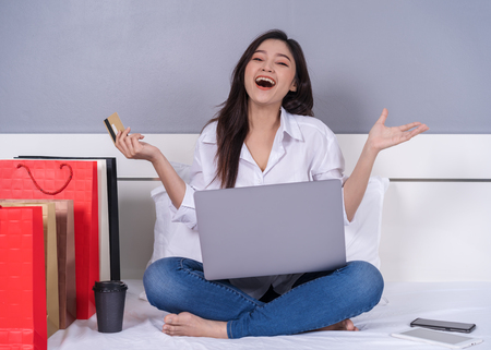 happy woman using laptop computer for online shopping with credit card on a bed Standard-Bild