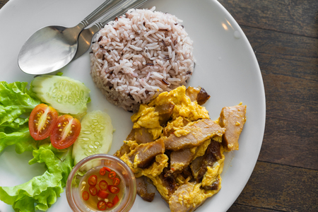 fried pork with egg and rice on plate