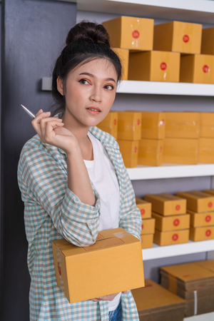 young woman entrepreneur thinking with parcel box, online business, prepare before delivery