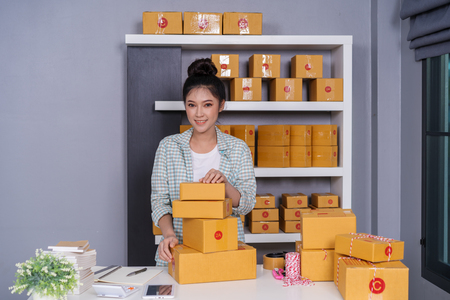 young woman entrepreneur with parcel boxes in her own job shopping online business at home 写真素材