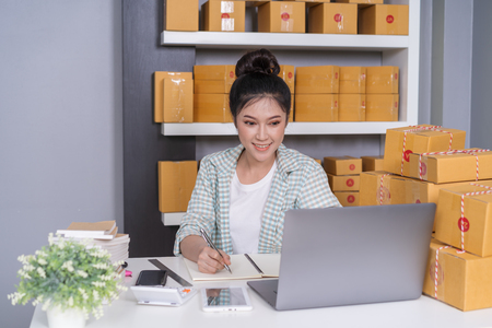 young woman entrepreneur checking and writting order with cardboard , SME business online prepare for delivery to customers in home office Stock Photo