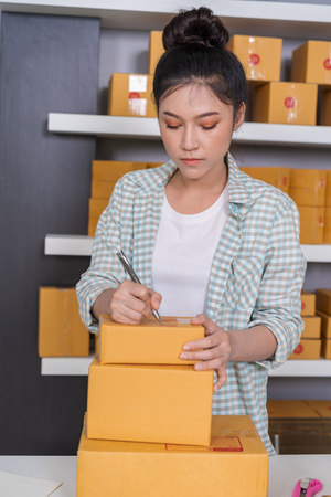 young woman entrepreneur writing on parcel box, online business, prepare before delivery