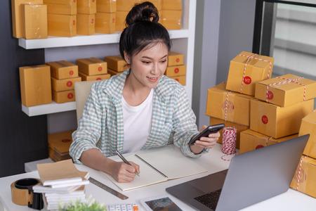 junge Unternehmerin, die Bestellung mit Karton prüft und schreibt, KMU-Geschäft online auf die Lieferung an Kunden im Homeoffice vorbereiten