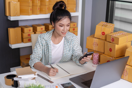 young woman entrepreneur checking and writting order with cardboard , SME business online prepare for delivery to customers in home office