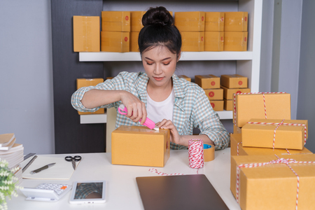young woman using cutter knife open delivery parcel