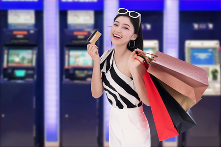 young happy woman holdking shopping bag and withdrawing money from credit card at ATM