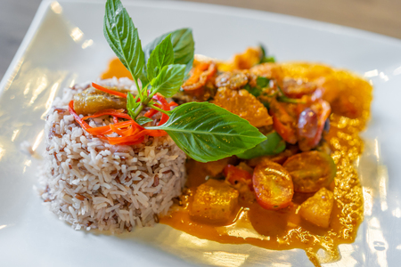 duck confit with red curry served with brown rice on a plate
