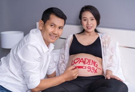 husband writting word loading 99% on belly of his pregnant wife