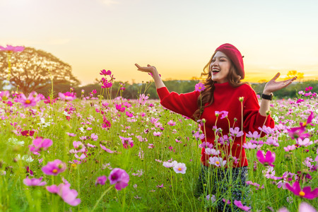 cheerful beautiful woman in cosmos flower field with sunset Banque d'images