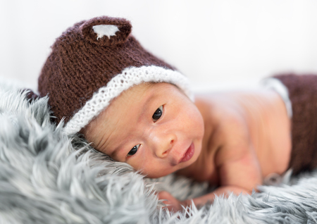 nouveau-né au chapeau d'ours sur un lit de fourrure