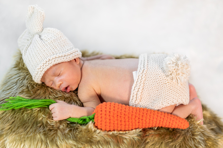 newborn baby in bunny costume sleeping on a fur bed 版權商用圖片