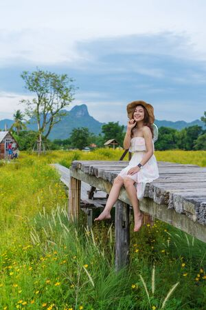 happy woman sitting on wooden bridge with yellow cosmos flower field