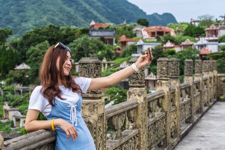 woman using smartphone to selfie a photo in Jiufen, Taiwan