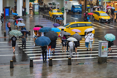 Taipei, Taiwan- 11 June, 2019: people crossing street in front of Ximending Shopping District with falling rain in Taipei, Taiwan. Ximending is the famous fashion, night Market and street food in Taipei.
