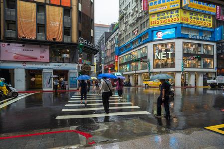 Taipei, Taiwan- 11 June, 2019: people crossing street in Ximen district with falling rain at Taipei, Taiwan
