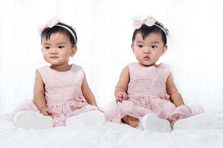 two twin babies in pink dress on a bed Banco de Imagens