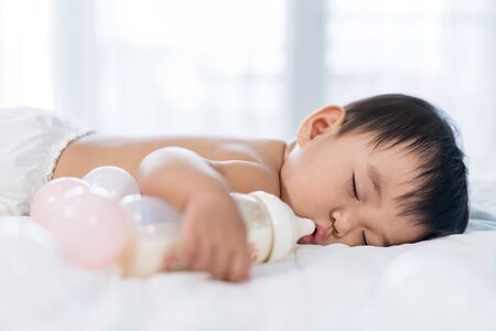 Baby sleeping on a bed after drinking bottle milk