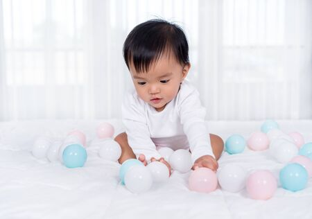 cheerful baby playing color ball on a bed