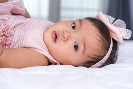 close up baby in pink dress on a bed Banco de Imagens