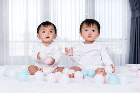 cheerful twin babies playing color ball on a bed