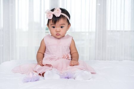 baby in pink dress on a bed Banco de Imagens