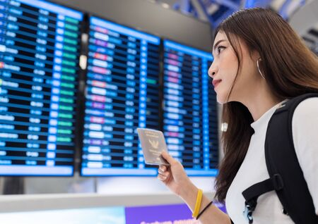 woman holding her passport with flight information board in the international airport