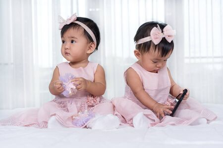 two twin babies in pink dress on a bed, one playing smart phone