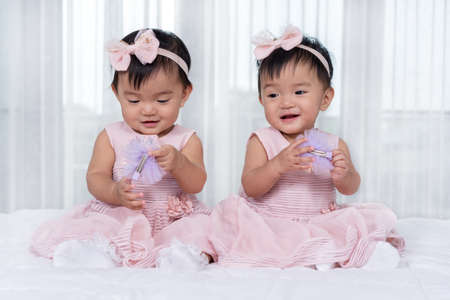 two twin babies in pink dress on a bed
