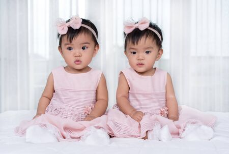 two twin babies in pink dress on a bed Banque d'images