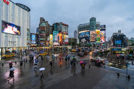 Taipei, Taiwan- 8 June, 2019: traffic and people walking on crosswalk with falling rain at Ximending in Taipei, Taiwan. Ximending is the famous fashion, night Market and street food in Taipei. Editorial