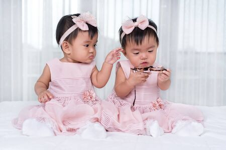 two twin babies in pink dress on a bed 写真素材