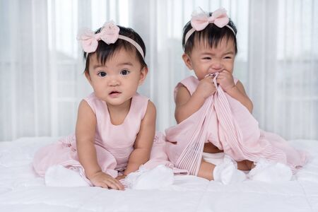 two twin babies in pink dress on a bed, one looking, one crying
