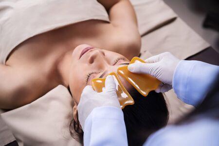 Jeune femme recevant une thérapie faciale guasa traditionnelle