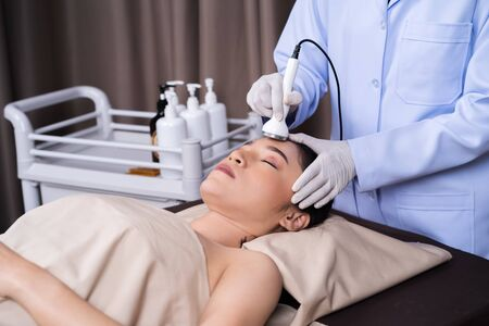 young woman receiving ultrasound facial beauty treatment skin care 写真素材