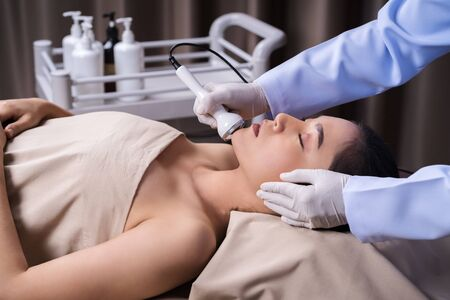 young woman receiving ultrasound facial beauty treatment skin care Stockfoto