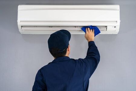 technician service cleaning the air conditioner with cloth 写真素材 - 129911767