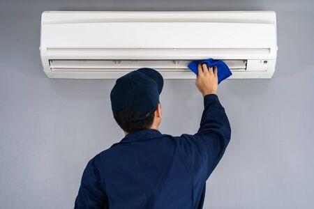 technicusservice die de airconditioner schoonmaakt met een doek