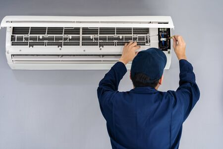 Electrician with screwdriver repairing the air conditioner indoors Foto de archivo