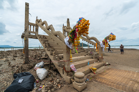 Lopburi - August 24,2019 : Unidentified people visit the ruins of Nong-Bua temple under the water of Pasak Jolasid Dam after the water reduced in Lopburi, Thailand