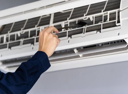 close up technician service using brush to cleaning the air conditioner indoors