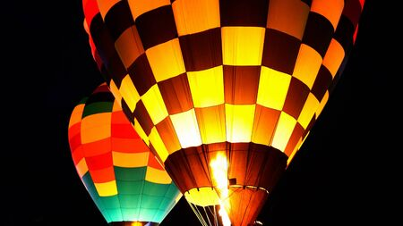 close up of hot air balloon with burner flame glowing at a night