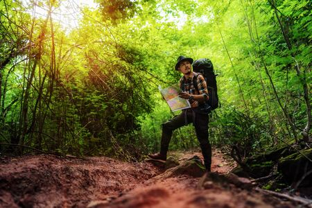 man traveler with backpack and map searching directions in the natural forest Archivio Fotografico
